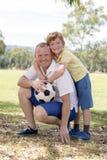 Pai feliz novo e 7 ou 8 anos entusiasmado do filho idoso que joga junto o futebol do futebol no jardim do parque da cidade que le Fotos de Stock