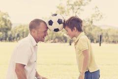 Pai feliz novo e 7 ou 8 anos entusiasmado do filho idoso que joga junto o futebol do futebol no jardim do parque da cidade que le Imagens de Stock Royalty Free