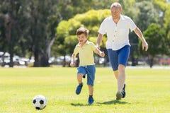 Pai feliz novo e 7 ou 8 anos pequenos entusiasmado do filho idoso que joga junto o futebol do futebol no jardim do parque da cida Fotografia de Stock