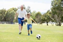 Pai feliz novo e 7 ou 8 anos pequenos entusiasmado do filho idoso que joga junto o futebol do futebol no jardim do parque da cida Fotografia de Stock Royalty Free
