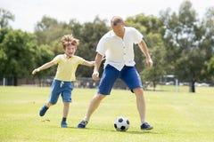 Pai feliz novo e 7 ou 8 anos pequenos entusiasmado do filho idoso que joga junto o futebol do futebol no jardim do parque da cida Imagens de Stock Royalty Free