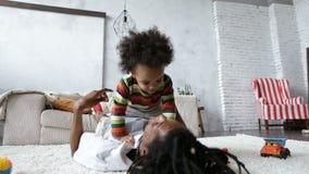 Pai feliz que aumenta seu filho bonito acima em casa vídeos de arquivo