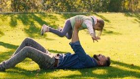 Pai feliz que guarda sua filha pequena nas mãos ao encontrar-se na grama verde filme