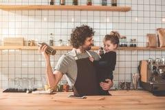 Pai feliz que joga com a menina pequena durante o trabalho no café Foto de Stock