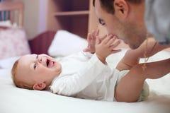 Pai feliz que joga com o bebê na cama Foto de Stock