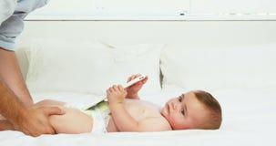 Pai feliz que joga com seu bebê em uma cama filme