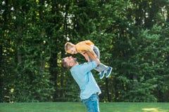 pai feliz que leva o filho pequeno de sorriso adorável fotos de stock royalty free