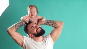 Pai feliz que leva sua filha infantil no pescoço isolado sobre o fundo azul vídeos de arquivo
