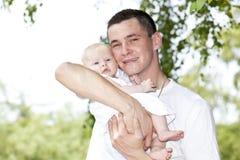 Pai feliz que prende seu bebé Fotos de Stock