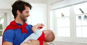 Pai feliz que veste um cabo e que guarda seu bebê com um cabo demasiado video estoque