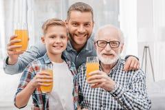 Pai, filho e avô guardando vidros do suco de laranja, do sorriso e da vista Fotos de Stock Royalty Free