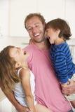 Pai Giving Children Cuddle em casa imagem de stock