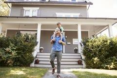 Pai Giving Son Ride em ombros fora da casa imagem de stock royalty free