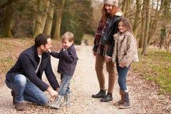Pai Helping Son To posto sobre a sapata durante a caminhada da família imagens de stock