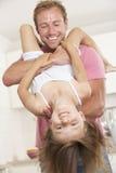 Pai Holding Daughter Upside para baixo em casa Imagem de Stock