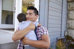 Pai Hugging Son Sitting em etapas fora da casa imagens de stock