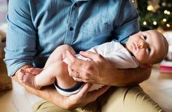 Pai irreconhecível com o bebê na frente da árvore de Natal Imagem de Stock