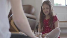 Pai irreconhecível e menina do retrato que jogam a xadrez que senta-se no fim do assoalho acima A filha ganha, ela é vídeos de arquivo