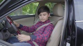 Pai irreconhecível que ensina seu filho conduzir o carro O menino prende seu seatbelt sob o controle do paizinho A criança e video estoque