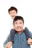 Pai japonês que dá a seu filho o reboque Fotografia de Stock Royalty Free