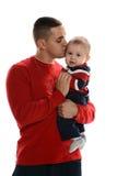 Pai latino-americano novo que beija seu filho fotografia de stock