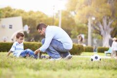 Pai Looking After Son ferido jogando o futebol Fotografia de Stock