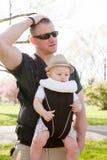 Pai Lost ou virada com o filho no portador de bebê imagens de stock