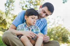 Pai loving Puts uma atadura no joelho de seu filho da virada fotos de stock royalty free