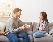 Pai loving que apresenta o presente à filha entusiasmado imagem de stock royalty free
