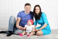 Pai, mãe e bebê felizes no tapete cinzento. Foto de Stock
