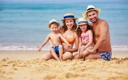 Pai, mãe e crianças felizes da família na praia no mar imagem de stock royalty free
