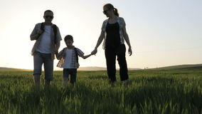 Pai, mãe e filho andando no campo no tempo do por do sol vídeos de arquivo
