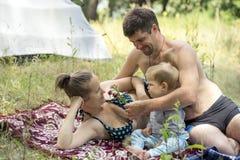 Pai, mãe e filho novos 1 3 anos que encontram-se na grama no piquenique O marido dá flores da esposa Imagem de Stock