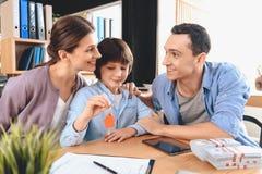 Pai, mãe e filho O filho está guardando chaves para o apartamento novo foto de stock royalty free