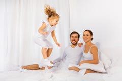 Pai, mãe e sua filha saltando na cama foto de stock