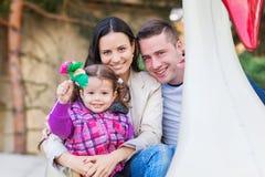 Pai, mãe, filha que aprecia o passeio da feira de divertimento, parque de diversões Fotografia de Stock Royalty Free