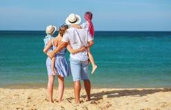 Pai, m?e e crian?as felizes da fam?lia para tr?s na praia no mar fotografia de stock royalty free