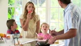 Pai Making Scrambled Eggs para o café da manhã da família na cozinha vídeos de arquivo