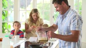 Pai Making Scrambled Eggs para o café da manhã da família na cozinha video estoque
