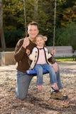 Pai novo com a filha no balanço. Imagem de Stock Royalty Free