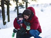 Pai novo com o filho exterior na paisagem do inverno, peo do estilo de vida fotos de stock