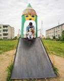 Pai novo com seu filho 1 3 anos no campo de jogos dentro Fotos de Stock Royalty Free