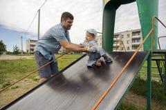 Pai novo com seu filho 1 3 anos no campo de jogos na vila Imagens de Stock Royalty Free