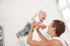 Pai novo com seus nove meses do filho idoso em casa Imagens de Stock Royalty Free