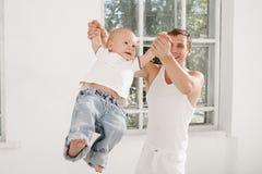 Pai novo com seus nove meses do filho idoso em casa Foto de Stock