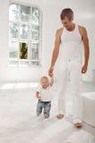 Pai novo com seus nove meses do filho idoso em casa Fotos de Stock Royalty Free