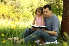 Pai novo com sua filha pequena que lê a Bíblia Imagens de Stock