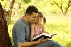 Pai novo com sua filha pequena que lê a Bíblia Imagens de Stock Royalty Free