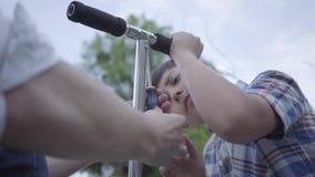 Pai novo do retrato que ensina seu filho fixar o close-up do 'trotinette' Opinião lateral o menino bonito com chave de fenda, ten filme