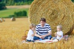 Pai novo e dois meninos pequenos da criança que têm o piquenique no feno fi Imagem de Stock Royalty Free